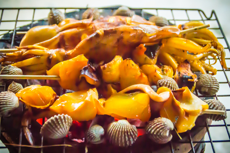 Grilled squids, mussels and clams on charcoal stove at night party. Seafood barbecue party with squid calamaris, mussels and clams are grilling on fire. BBQ concept, selective focus.