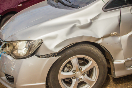 Close-up front of new silver car distorted by accident