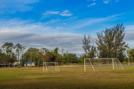 Stade de football local avec poteau de but et fond de nuages bleu et ciel bleu dans la zone rurale. Terrain de soccer à l'école provinciale avec herbe verte, but et fond de ciel bleu.