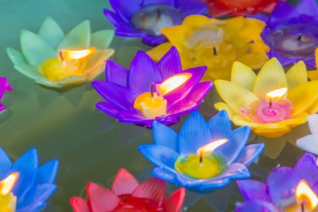 Colorful lotus flower with burning candles are floating on the colorful lotus flower with burning candles are floating on the water to worship the buddha with mightylinksfo