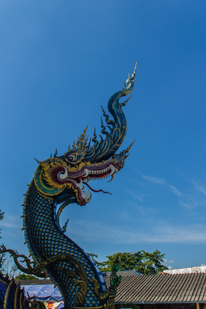 Beautiful blue naga sculpture with blue sky and white cloud on the sunny day at the public temple, Wat Rong Sua Ten, Chiang Rai, Thailand. Naga is a very great snake, found in the Buddhism temples. Stock Photo
