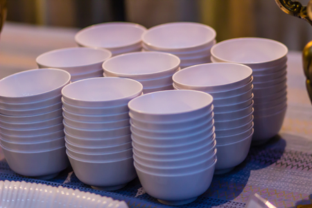 Stack of clean white bowl on a table for a buffet in the restaurant. Cleaned white soup or salad bowls in commercial kitchen of restaurant. Pile of clean empty cups on the table prepare for party.