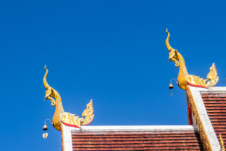 Beautiful golden naga sculptures on the church roof under the blue sky background at Wat Phra That Doi Tung, one of which is believed to contain the left collarbone of Lord Buddha. Stock Photo - 102474509