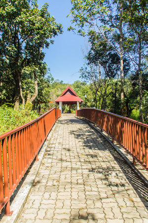 Walkway into the temple in the forest that constructed with brick floor and steel fence.