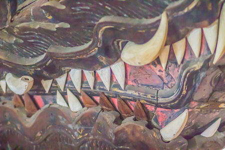 Beautiful traditional Thai style craving patterned of wooden royal barge. Golden monster head with fangs craved pattern of Suwan Hera thai royal barge. Stock Photo