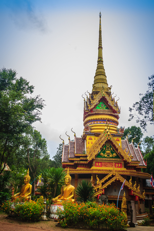 Beautiful golden pagoda with decorative Thai style fine art at public Buddhist Wat Phu Phlan Sung temple, Nachaluay, Ubon Ratchathani, Thailand.
