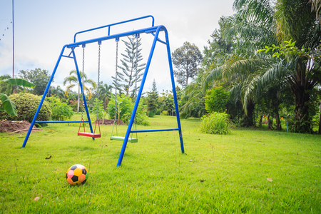Playground equipment in the backyard for kids with soccer goal net and football on green grass field background. Stock Photo