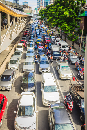 Bangkok, Thailand - August 21, 2017: Many cars are stop and waiting for the green traffic light at a junction during rush hour and traffic jam on Sathorn Road in Bangkok