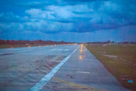 Final approach to landing and taking-off on a runway in the evening flight. Skid marks on at the airport runway after sunset. Stock Photo