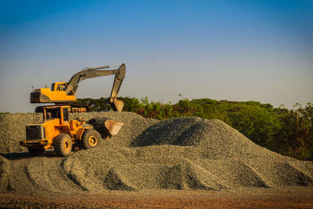 Yellow wheel loader and excavator are working in quarry against the background of crushed stone storage. Stok Fotoğraf - 104549849