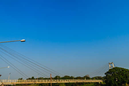 Suspension bridge spanning across Nan river to Phichit railway station in Muang district of Phichit province with blue sky and sunshine. Phichit is a province of Thailand and far 330 km from Bangkok.