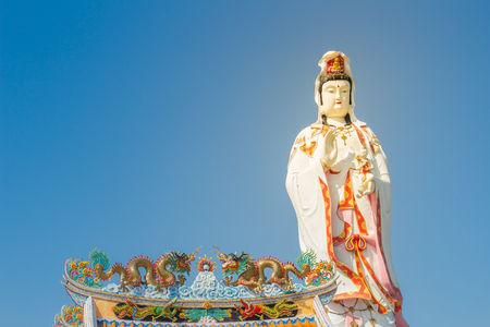 Giant white Guanyin statue with blue sky background. Guanyin or Guan Yin is an East Asian bodhisattva of Mahayana Buddhists and Chinese folk religions, also known as the