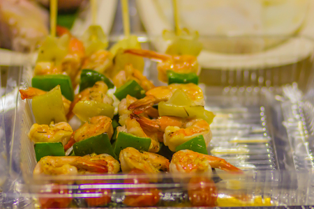 Sizzling shrimp kebabs for sale at the seafood market. Barbecue shrimps with paprika chili in the skewer that ready to eat and bring back home.