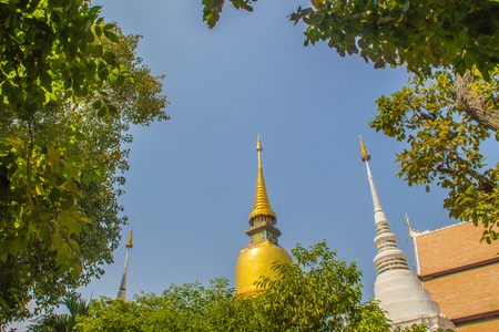 Beautiful golden and white pagodas in Sri Lankan style at Wat Suan Dok (flower garden temple) with blue sky background. Wat Suan Dok, also known as Wat Buppharam, built in 1370, Chiang Mai, Thailand. Imagens