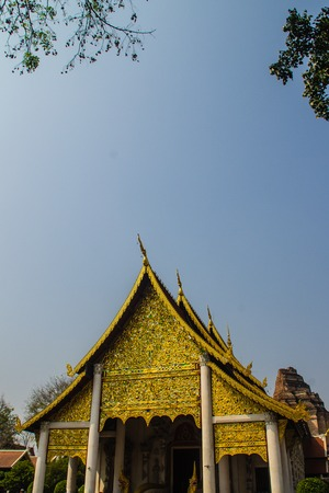 Lannas style golden patterned background on the Buddhist church gable end. Thai golden pattern background crafted on the gable in the Buddhist temple with Lanna style at Wat Chedi Luang, Chiang Mai. Stock Photo