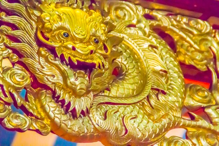 Beautiful golden chinese dragon head sculpture shining in the public Chinese temple. Chinese dragons, also known as East Asian dragons, are legendary creatures in Chinese mythology, Chinese folklore.
