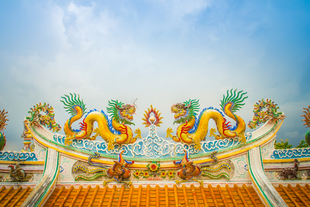 Beautiful large grimace dragons crawling on the decorative tile roof in Chinese temples. Colorful roof detail of traditional Chinese temple with dragon statue on blue sky background. Selective focus. Stock Photo