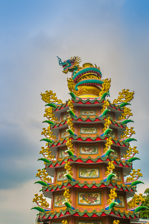 Colorful statue of Chinese dragon wrapped around the pillar. Beautiful statue of dragon carved around temple pole in Chinese public temple. Imagens
