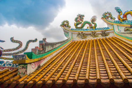 Beautiful large grimace dragons crawling on the decorative tile roof in Chinese temples. Colorful roof detail of traditional Chinese temple with dragon statue on blue sky background. Selective focus. Imagens