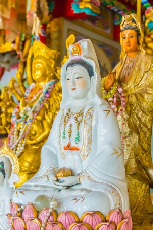 Golden guanyin statue in the public Chinese temple. Guanyin or Guan Yin is an East Asian bodhisattva with compassion and venerated by Mahayana Buddhists and followers of Chinese folk religions. Imagens