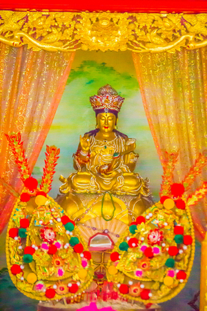 Golden guanyin statue in the public Chinese temple. Guanyin or Guan Yin is an East Asian bodhisattva with compassion and venerated by Mahayana Buddhists and followers of Chinese folk religions. Editorial