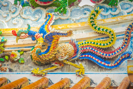Colorful Phoenix bird flying on the decorative tile roof in Chinese temples. Beautiful roof detail of traditional Chinese temple Imagens