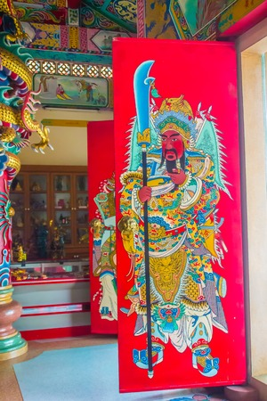 Colorful red Guan Yu painting with blade as the guardian on the door in the public Chinese temple. Guan Yu is the god warrior in the Three Kingdoms period. 에디토리얼