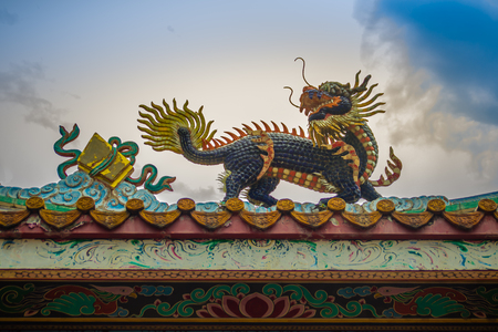 Beautiful Chinese dragon-headed unicorn statue on the temple roof. Kylin or Kirin on roof in Chinese temple. Imagens