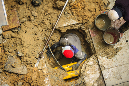 Technician worker is repairing the underground water pipe broken. Unidentified plumber is digging for repair the underground pipe cracked.