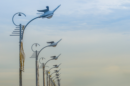 Row of the street lamps in bird shaped with the white clouds background. Perspective street lamps aligned with beautiful blue sky in background.