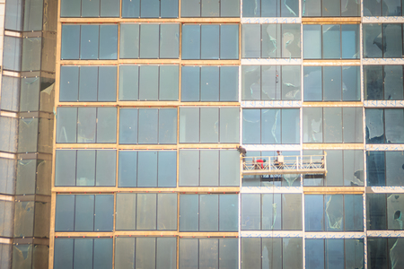 Construction workers on a suspended cradle platform on a skyscraper glass facade. Suspended cradle is similar to temporary suspended scaffolds for workers to work outside the skyscraper building.
