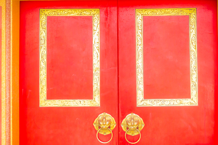 Golden door knocker in the shape of lion with ring on a red wooden door. Close up wooden Chinese style red door with lion head doorknob. Imagens