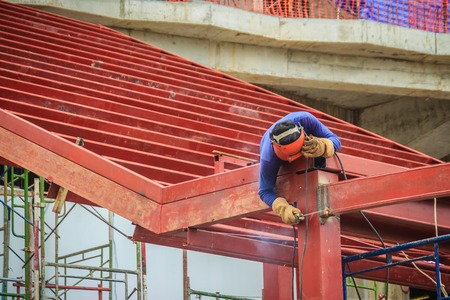 Risky welder while climbing and welding on top of the steel roof structure work at the building construction site. Skilled worker is welding on the high steel structure at the construction project.