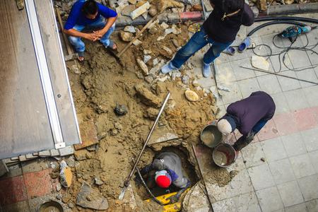 Technician worker is repairing the underground water pipe broken. Unidentified plumber is digging for repair the underground pipe cracked.