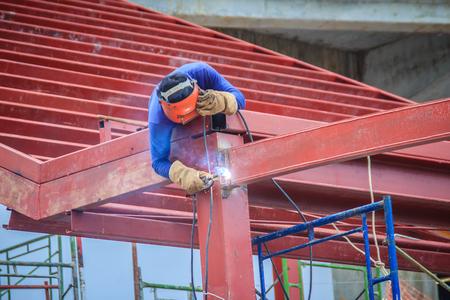 Saldatore rischioso durante l'arrampicata e la saldatura sulla parte superiore della struttura del tetto in acciaio lavora in cantiere. L'operaio specializzato sta saldando sull'alta struttura in acciaio al progetto di costruzione. Archivio Fotografico