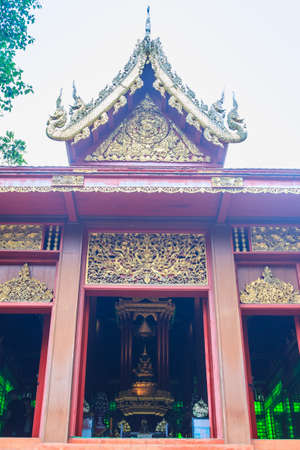 Beautiful Phra Uposatha or Ubosoth in Chiang Saen style with nicely carved wooden structure with unique carved doors at Wat Phra Kaew, Chiang Rai, Thailand.