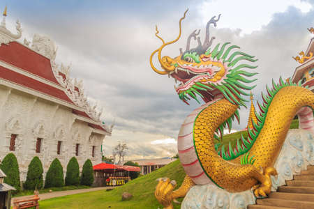 Yellow dragon head at Wat Huay Pla Kang, bublic Chinese temple in Chiang Rai Province, Thailand with dramatic blue sky background. Stock Photo