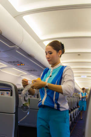 Bangkok, Thailand - June 13, 2017: Air hostess flight attendant of the Bangkok airways is explain the usage safety equipment to the passengers on the plane, demonstrate safety procedures to passengers