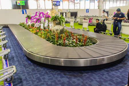 Chiang Rai, Thailand - June 13, 2017: Baggage conveyer with beautiful orchid decoration at Mae Fah Luang - Chiang Rai International Airport, Chiang Rai, Thailand.