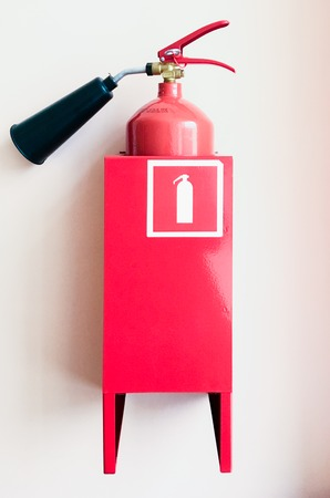A fire extinguisher hanging on the wall in the room