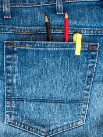 Red and black pencils and yellow marker in the back pocket of blue jeans Фото со стока