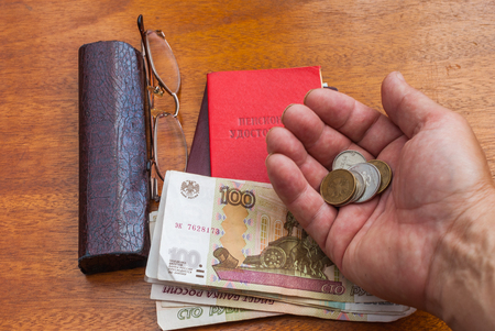 Mans hand holding money, glasses and pension certificate on a wooden surface.