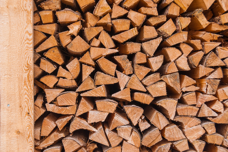 Chopped wood piled in a woodpile and prepared for heating in winter Alpine Switzerland