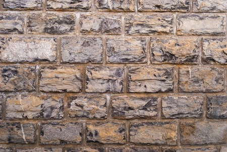 Stone wall grey brick stones texture background.