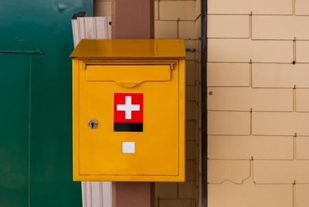 Yellow mailbox Swiss postal service mounted on a brick wall. Archivio Fotografico