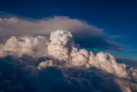 top view of the clouds and the blue sky from the plane window, the background of nature. Archivio Fotografico