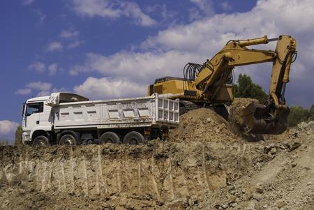 Excavator loads dump truck soil on the construction site.