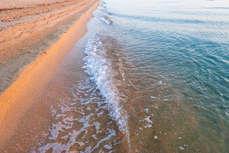 Beautiful deserted sandy beach with small waves of surf. Stock Photo