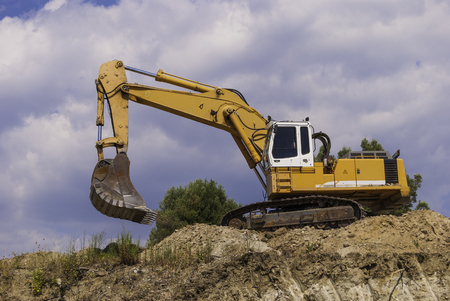 Excavator on the construction site is preparing to load the soil. Imagens