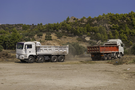 loaded modern dump trucks transporting construction soil from the construction site. Stock fotó